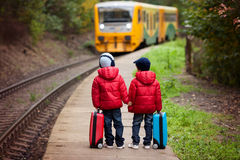 Two boys on a railway station, waiting for the train with suitca Stock Images