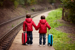 Two boys on a railway station, waiting for the train with suitca Royalty Free Stock Images