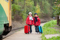 Two boys on a railway station, waiting for the train with suitca Royalty Free Stock Photography