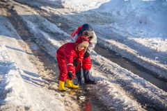 Two boys playing with boat an the creek. Two boys in rainboots playing with toy boat an the creek of melting snow at sunny spring day, outdoors royalty free stock image