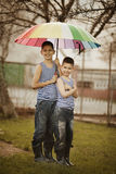 Two boys with rainbow umbrella in park Stock Photo