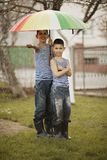 Two boys with rainbow umbrella in park Royalty Free Stock Photos