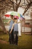 Two boys with rainbow umbrella in park Stock Photo