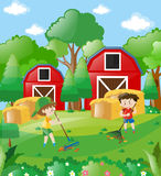 Two boys raking dried leaves in farm Stock Images