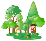 Two boys raking leaves in forest Stock Photos
