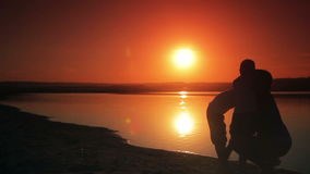 Two boys ran to a happy mother and held her on the. Beach at sunset silhouette  of family stock footage