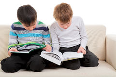 Two boys reading big book. Two happy boys reading big book solated on white background Stock Photos