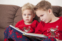 Two boys reading book. On the couch Stock Photo