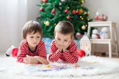 Two boys, reading a book in front of Christmas tree. At home Royalty Free Stock Image