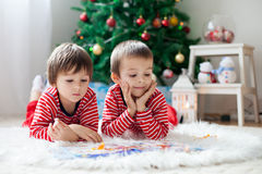 Two boys, reading a book in front of Christmas tree. At home Royalty Free Stock Images