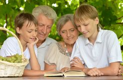 Two boys reading. A book at nature with their grandparents Stock Photo