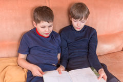 Two boys reading book. Siiting on the sofa Stock Images