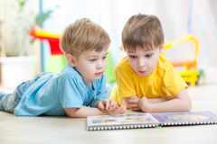 Two boys reading a book together. Children boys play together lying on floor Stock Photo