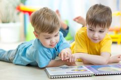 Two boys reading a book together. Two kids boys reading a book together Royalty Free Stock Images