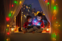 Two boys, reading book on the window Stock Photography