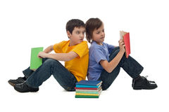 Two boys reading books. Two happy boys sitting on the floor and reading books Stock Image