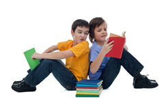 Two boys reading books. Two happy boys sitting on the floor and reading books Royalty Free Stock Image