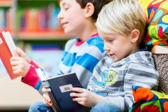 Two boys reading books in the library. Having fun together Royalty Free Stock Images