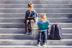 Two boys reading, doing homework outdoors. Back to school concept. Royalty Free Stock Photography