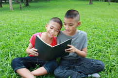 Two boys reading in the park. Stock Image