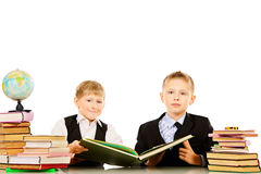 Two boys reading. Two schoolboys do their lessons together at the table. Isolated over white Royalty Free Stock Photos