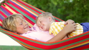Two Boys Relaxing In Garden Hammock Together stock video