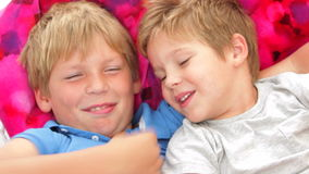 Two Boys Relaxing In Garden Hammock Together stock video footage