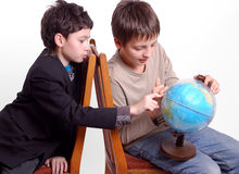 Two boys researching globe isolated on white Royalty Free Stock Photos