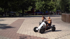 Two boys ride on Kids pedal car. Town Square stock video