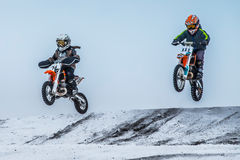 Two boys riders motorcycle flying after jumping over mountain Royalty Free Stock Photos