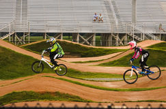 Two boys riding bicycles in an outdoor BMX track Stock Image
