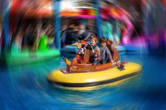 Two boys, riding boat in amusement park Stock Photos