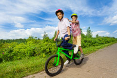 Two boys riding same bike and both stand Royalty Free Stock Image