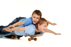 Two boys riding on a skateboard Stock Photos