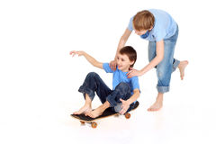 Two boys riding on a skateboard Royalty Free Stock Images