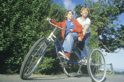 Two boys riding a three wheeled bicycle Royalty Free Stock Photos