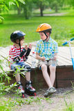 Two boys with rollers and scooter sit on a wooden platform Stock Photos