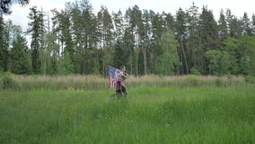 Two boys run across the clearing with US flag stock video footage