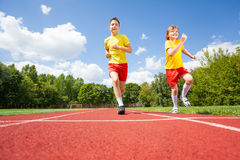 Two boys run while competing to each other Royalty Free Stock Images