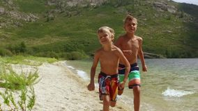 Two boys run a race on the beach in slow motion. Two boys run a race on the beach on the shore of a mountain lake in slow motion stock footage