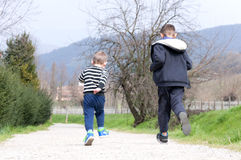 Two boys run on rural road Stock Image