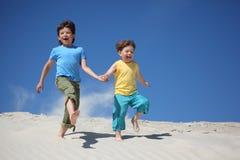 Two boys run on sand stock photography