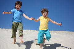 Two boys run on sand Stock Photo