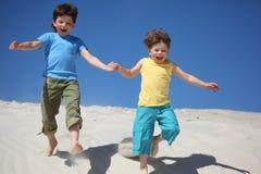 Two boys run on sand stock photo