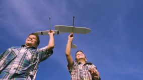 Two boys running with airplanes against blue sky stock footage