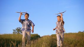 Two boys running with airplanes at the hill stock video footage