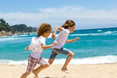 Two boys running on beach. Stock Photos
