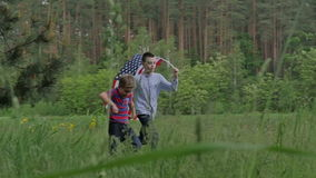 Two boys running in the forest with US flag. Two boys run across the meadow with US flag. Side view boys running with the US Flag in the forest. Children are stock footage