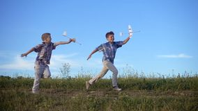 Two boys running with his airplanes at the field. Slow motion stock footage