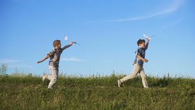 Two boys running with his airplanes at field stock footage